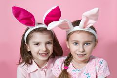 Two little friends, with Bunny ears, depict Easter rabbits. The symbol of Easter.Two girls with ears on their heads. On a pink background stock image