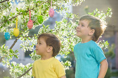 Two little friends in Easter hunting eggs in spring garden, outdoors. On warm sunny day with blooming trees  background Stock Photos