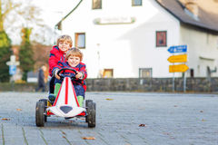 Two little friends kids in red jackets driving fast race car tog Royalty Free Stock Images