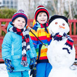 Two little friends making a snowman, playing and having fun with Royalty Free Stock Photos