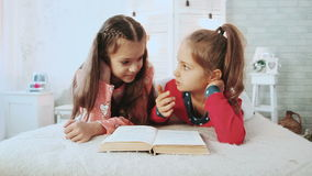 Two little friends, are in pajamas and they reading book. They talk and discuss the book. Two cute little girls in pajamas reading a book stock video footage