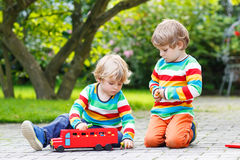 Two little friends playing with red school bus Stock Images