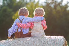 Two little friends sitting on hay bale Stock Photo