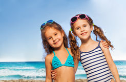 Two little friends in swimwear at the seashore. Two little smiling friends in swimwear and sunglasses at the seashore Royalty Free Stock Image