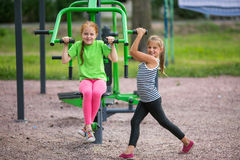 Two little fun girls is engaged in sports equipment Stock Photos