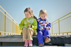 Two little funny girls on a ladder Stock Image