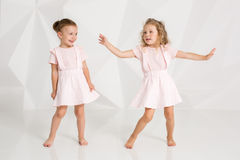 Two little funny and laughing girl in gently pink dresses posing in white studio Royalty Free Stock Images