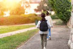 Young girls walking outdoors in summer city street at sunset or sunrise time. royalty free stock photography