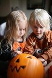 Two Little Girl Children Digging Through Halloween Pumpkin Bucket for Candy. Two little girl children are digging through a pumpkin bucket of Halloween candy stock photos