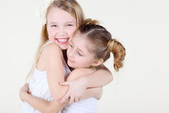 Two little girl in clean white clothes hugged strongly. Royalty Free Stock Photos