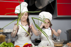 Two little girl cook Stock Photos