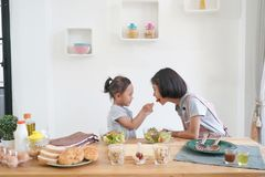 Two little girl eating salad and cooks in the kitchen stock photos