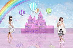 Two little girl in front of a pink fairy castle Royalty Free Stock Photo