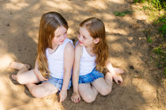 Two little girl girl friends hugging in the forest Royalty Free Stock Images