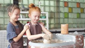 Two little girl having fun playing with clay on a pottery wheel. stock video footage
