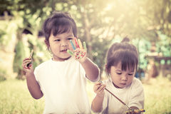 Two little girl having fun to paint on hands Stock Photography