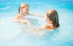 Fun for two little girls in pool. stock images