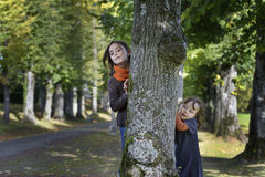 Two little girl looking from behind a tree stock photography