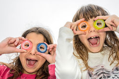 Two little girl are looking through the circles of a scotch tape Royalty Free Stock Image