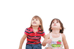 Two little girl looking up. Two and four years old, isolated on white background Royalty Free Stock Photography