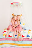 Two little girl lying on a pile of mattresses Stock Image