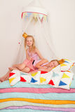 Two little girl lying on a pile of mattresses Stock Photography