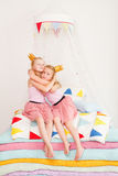 Two little girl lying on a pile of mattresses. Stock Photos