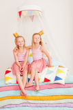 Two little girl lying on a pile of mattresses Stock Images