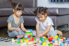 Two little girl play with wooden toys blocks on the floor, build. Ing towers at home Royalty Free Stock Photography
