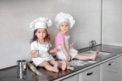 Two Little girl preparing cookies in kitchen at home royalty free stock images