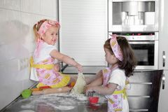 Two Little girl preparing cookies in kitchen at home royalty free stock photo