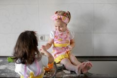 Two Little girl preparing cookies in kitchen at home royalty free stock photos
