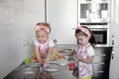Two Little girl preparing cookies in kitchen at home stock image