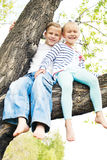 Two little girl sitting on a tree and waving her bare fee Stock Photography