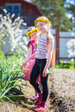 Two little girl working in the garden watering first spring flowers on a sunny warm day. stock images