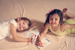 Two little girl writing on bed. royalty free stock photos