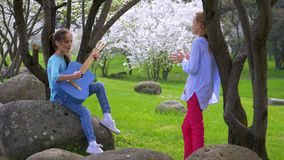 Two little girlfriend playing on jeans guitar and singing in city park beautiful scenery. Two little girlfriend playing on jeans guitar and singing in city park stock footage