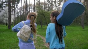 Two little girlfriend walk in Park with acoustic guitar on shoulder. concept emotions and joy. Two little girlfriend walk in the Park with acoustic guitar on stock video footage