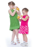 Two little girlfriends drink orange juice. royalty free stock images