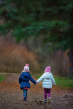 Two little girlfriends. Hand in hand in the forest Royalty Free Stock Photos