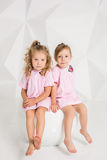 Two little girlfriends in the same pink dresses sitting on a chair in a studio with white walls Royalty Free Stock Photography