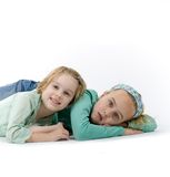 Two Little Girls. Two Sisters laying on the ground.  Isolated against a white background Royalty Free Stock Image