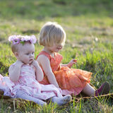 Two little girls. Sitting on the grass Stock Images