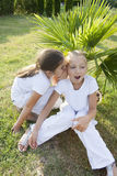 Two little girls. The little girl tells a secret to the friend Stock Photos