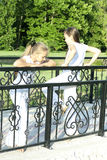 Two little girls. Little girl talks to the friend on the bridge Royalty Free Stock Photography