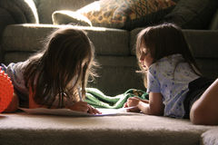 Two Little Girls. Lay on the floor drawing Royalty Free Stock Images