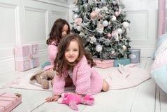 Two little girls around the Christmas tree stock photo
