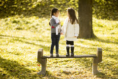 Two little girls at the autumn park. Two little girls on the bench in the autumn park Stock Images
