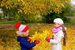 Two little girls in autumn park with leafs Royalty Free Stock Photos