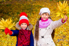 Two little girls in autumn park with leafs Royalty Free Stock Images